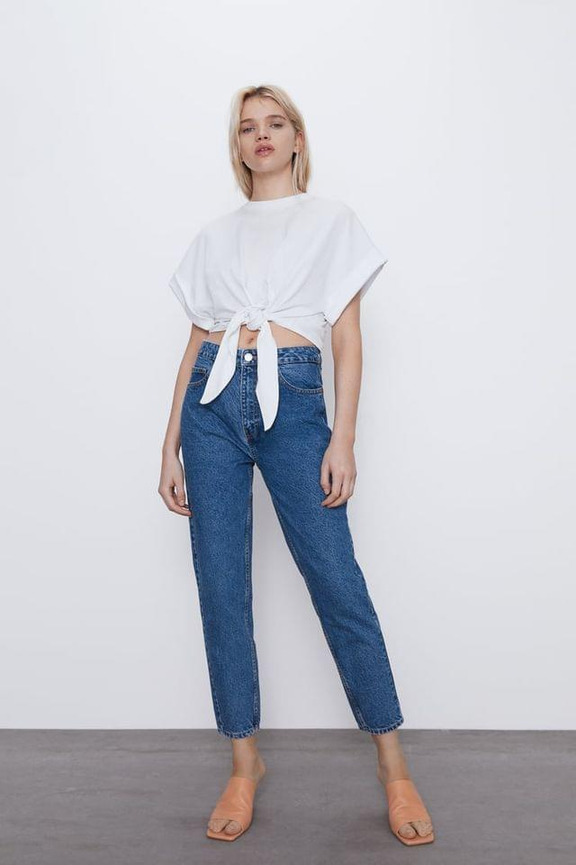 WOMEN ROUND NECK TOP WITH SHORT CUFFED SLEEVES. KNOT DETAIL AT FRONT HEM. BR/ BR/ MODEL HEIGHT 5 10 (177 CM)
