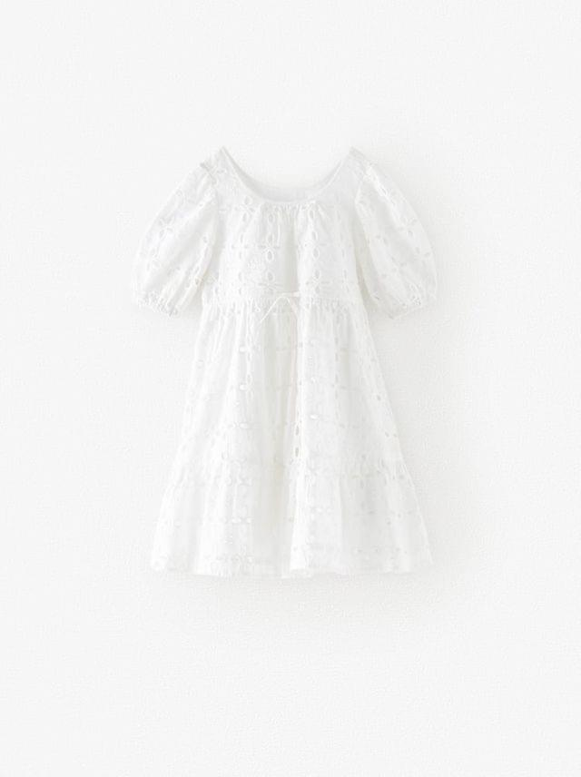 KIDS ROUND NECK SHORT SLEEVE DRESS. SEAM AT WAIST WITH ADJUSTABLE DRAWSTRING. RUFFLED HEM. EMBROIDERED EYELET MOTIF.
