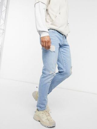 slim jeans in light wash blue with heavy rips