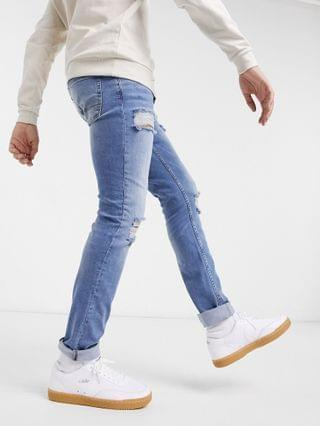 organic skinny jeans in mid wash blue with knee rip