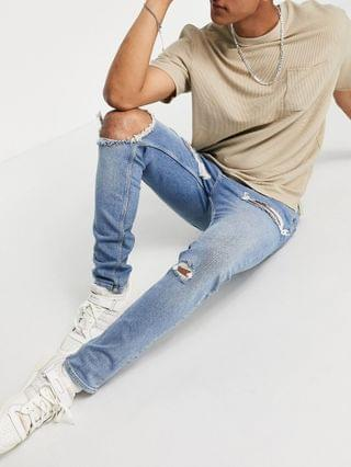 skinny jeans with rips and destroyed hem in vintage mid wash blue