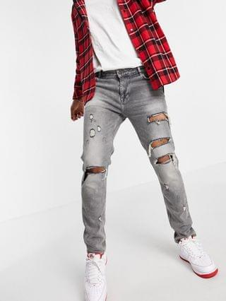skinny jeans with heavy rips in washed gray